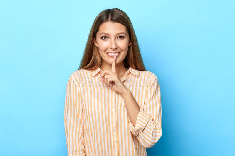 Young cheerful happy woman asking to be quiet with finger on lips. Silence, secret , body language concept.isolated blue background, studio shot royalty free stock photography