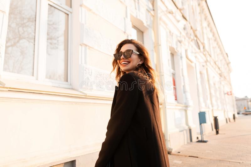Young cheerful hipster woman with a positive smile in black sunglasses in an elegant coat posing near a white vintage building. In the city on a bright sunny royalty free stock photos