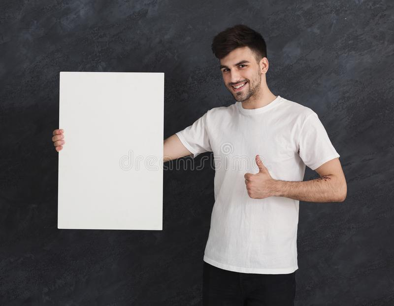 Young cheerful man with blank white paper royalty free stock images