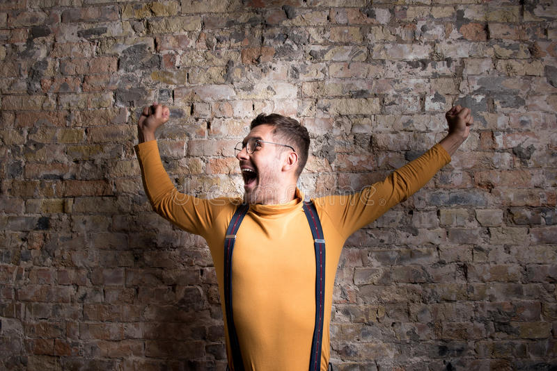 Young cheerful man celebrating his achievement stock image