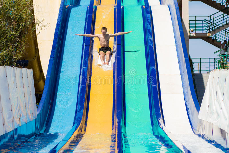Young cheerful man has fun on vacation on a slide in the water park royalty free stock photo