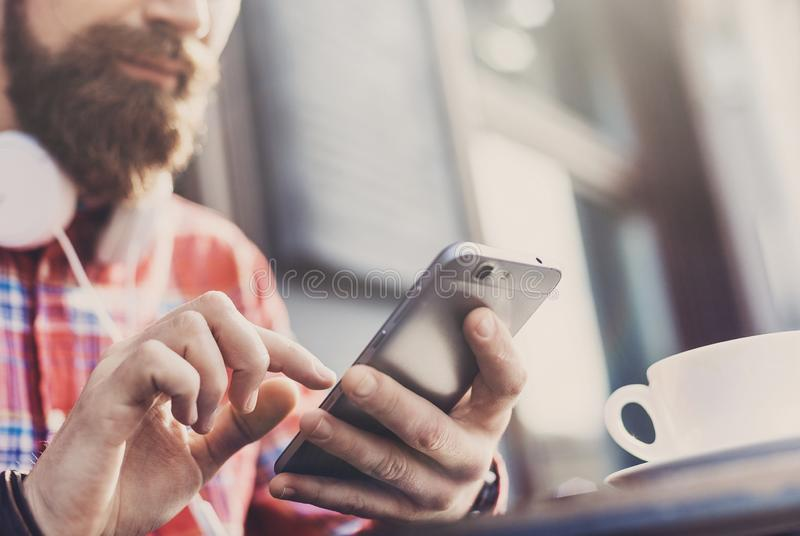 Young man texting on his smartphone in the city. Close up of cheerful adult using mobile phone in a cafe. Young cheerful man texting on his smartphone in the royalty free stock photography