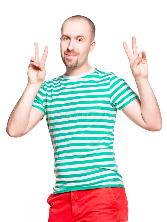 Young cheerful man with v sign in striped white and turquoise t-shirt and orange jeans isolated on white royalty free stock image