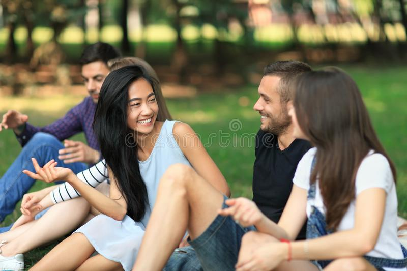 Young cheerful men and women talking in park stock photos