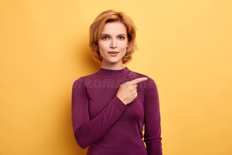 Young cheerful pleasant woman pointing side way by finger stock photos