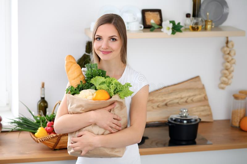 Young cheerful smiling woman is ready for cooking in a kitchen. Housewife is holding big paper bag full of fresh. Vegetables and fruits and looking at the stock images