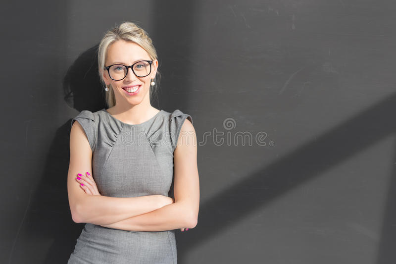Young cheerful teacher standing in front of blackboard with arms crossed stock photo