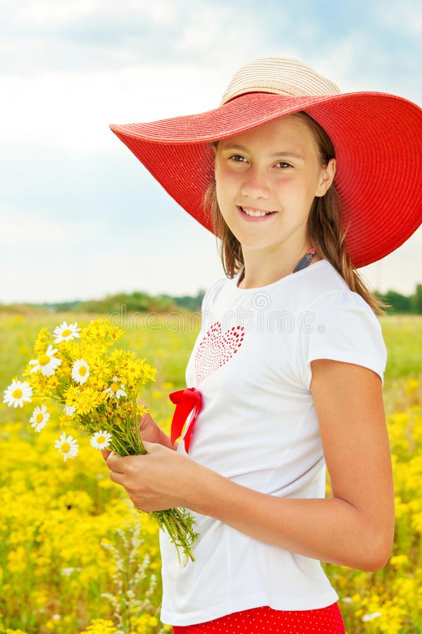 Young cheerful teenage girl with bouquet of yellow flowers. royalty free stock photos