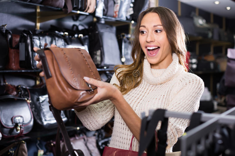 Young cheerful woman buying leather purse in shop stock image