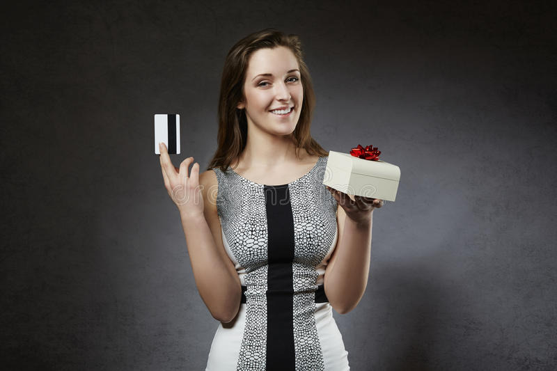 Young cheerful woman holding credit card and gift box royalty free stock image