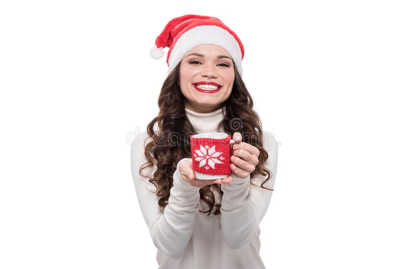 young cheerful woman in santa hat holding a coffee cup, royalty free stock photography