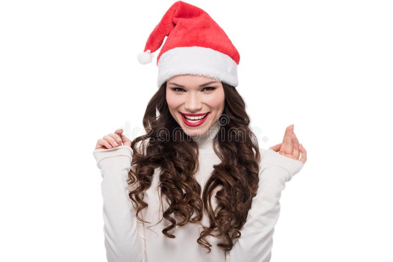 young cheerful woman in santa hat posing with arms raised, stock images
