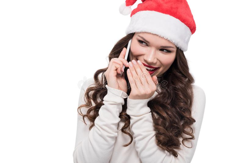 young cheerful woman in santa hat talking on smartphone, royalty free stock images
