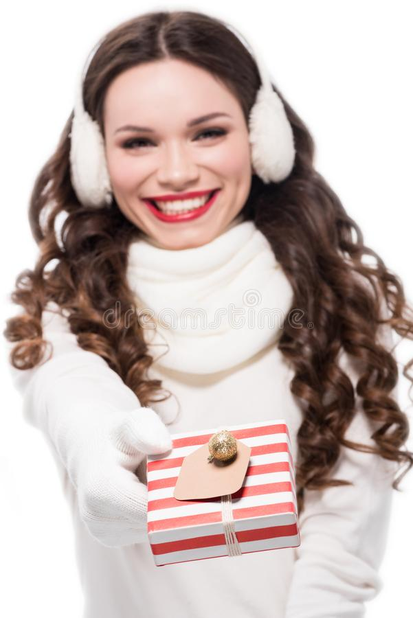 young cheerful woman in scarf, gloves and earmuffs handing a small present , stock photography
