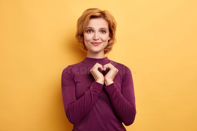 Young cheerful woman showing a heart gesture with palms. Isolated on yellow background. girl showing her love , affection, feeling and emotion . body langauge royalty free stock photos
