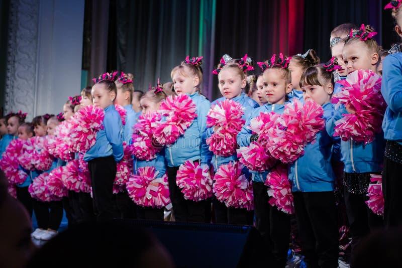 Young cheerleaders perform at the city cheerleading championship. Kamenskoye, Ukraine - October 14, 2018: Championship of the city of Kamenskoye in cheerleading stock images