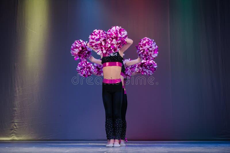 Young cheerleaders perform at the city cheerleading championship. Kamenskoye, Ukraine - October 14, 2018: Championship of the city of Kamenskoye in cheerleading stock image