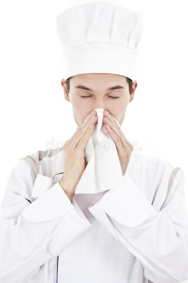 Young chef man with cold, blowing her nose royalty free stock photos