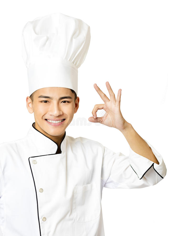 Young chef with ok gesture on white stock photography