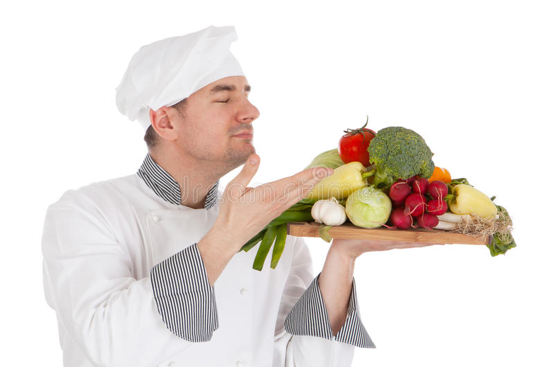 Young chef smelling aroma of vegetable. Isolated on white background royalty free stock images