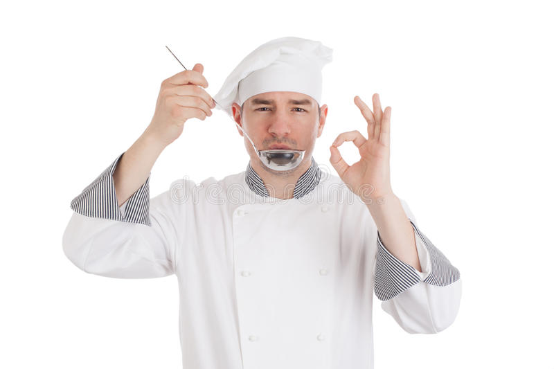 Young chef tasting food from ladle royalty free stock image