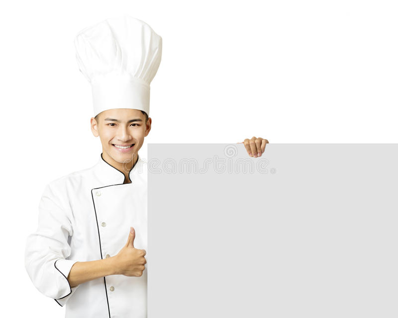 Young chef with thumb up and showing empty board royalty free stock images