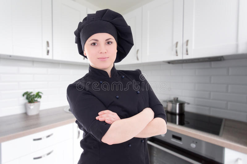 Young chef woman in black uniform posing in modern kitchen stock image