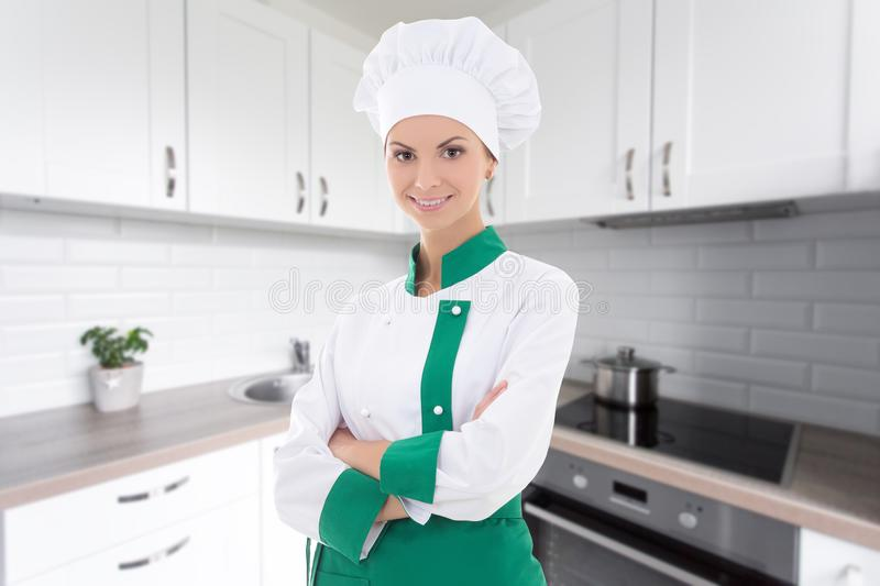 Young chef woman in uniform standing in modern kitchen. Young beautiful chef woman in uniform standing in modern kitchen royalty free stock image