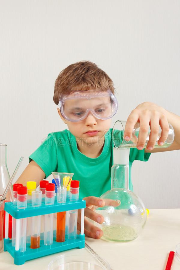 Young chemist in safety goggles doing chemical experiments in laboratory. Young chemist in safety goggles doing chemical experiments in the laboratory stock image