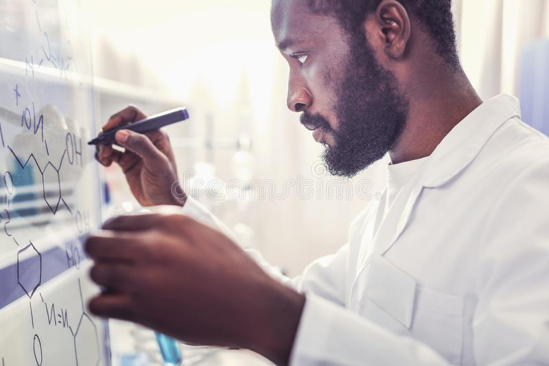 Seriously looking young chemist writing chemical formula. Young chemist. Seriously looking young chemist wearing white uniform writing difficult chemical formula royalty free stock image