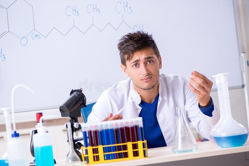 The young chemist sitting in the lab royalty free stock image