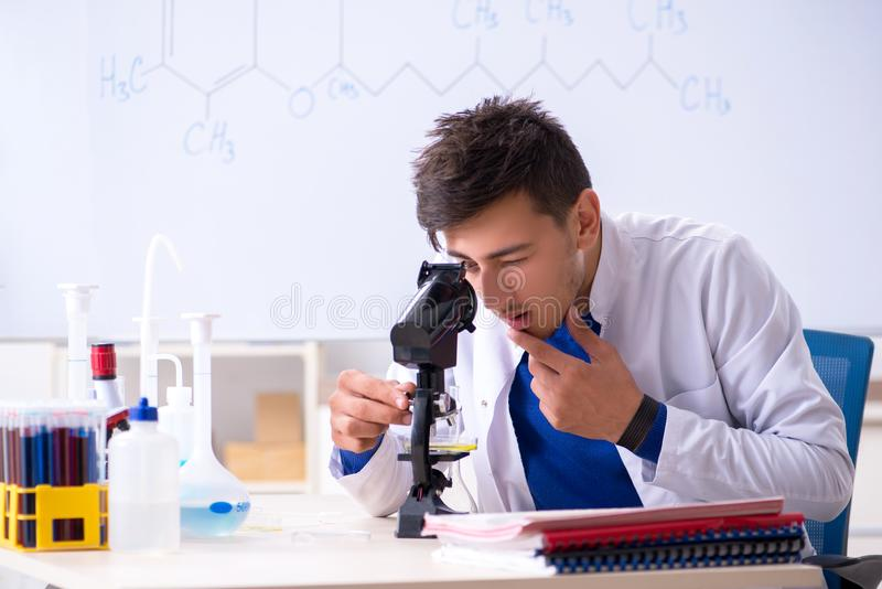 The young chemist sitting in the lab royalty free stock photo