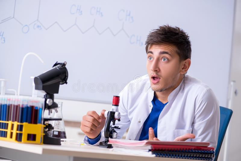 The young chemist sitting in the lab stock images