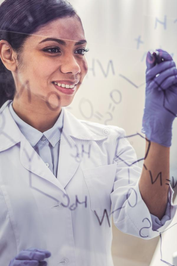Young chemist wearing glove writing molecular chain. Young chemist. Young charming dark-haired chemist wearing glove feeling occupied while writing molecular stock photography
