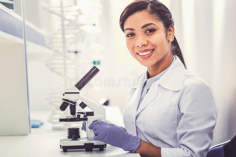 Young chemist wearing white uniform sitting near microscope. Near microscope. Young promising skillful chemist wearing white uniform feeling impressed while stock image