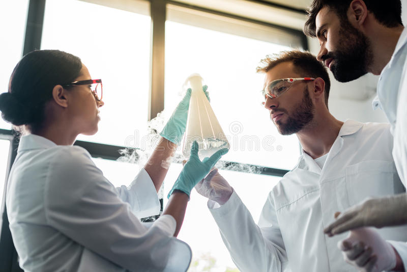 Young chemists in eyeglasses and white coats making experiment in laboratory stock images