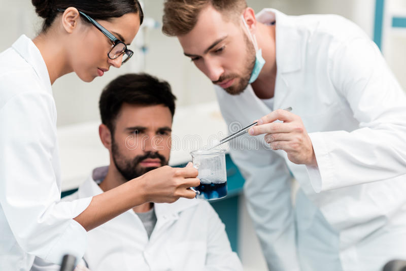 Young chemists in lab coats making working with reagent in laboratory royalty free stock photography