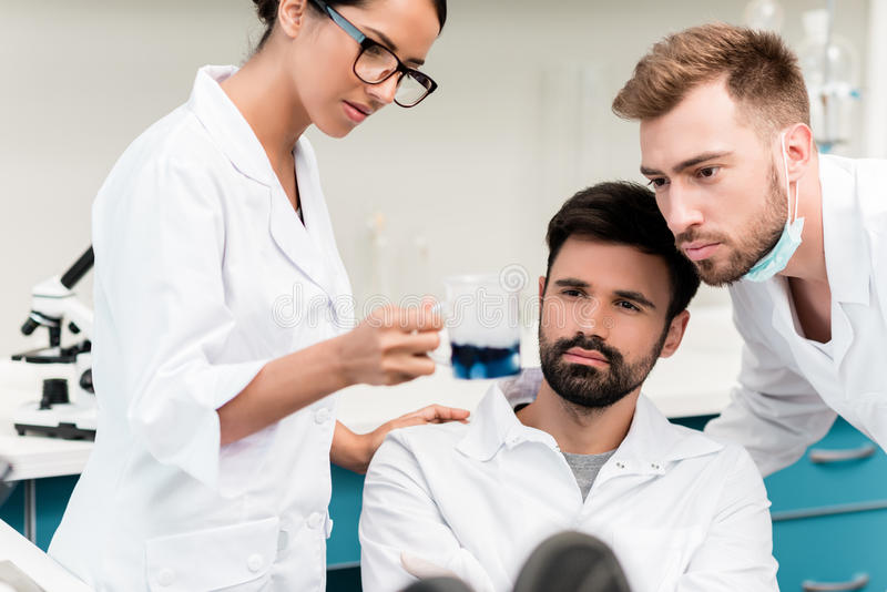 Young chemists in lab coats making working with reagent in laboratory stock images