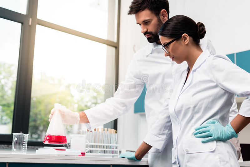Young chemists in white coats making experiment while working in laboratory. Focused young chemists in white coats making experiment while working in laboratory stock image