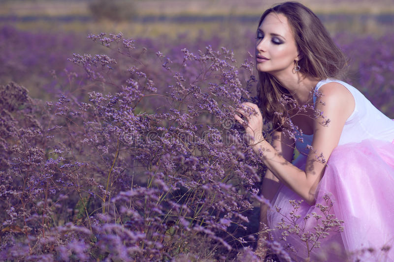 Young chic woman with artistic make up and long flying hair smelling violet flowers with closed eyes. On the field. Perfume and aroma concept. Outdoor shot stock photography