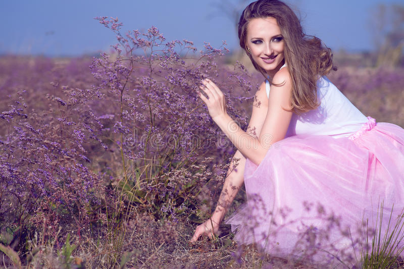Young chic woman with long waving hair and artistic make up sitting on the field of violet flowers looking aside and smiling. Perfume and aroma concept stock photography