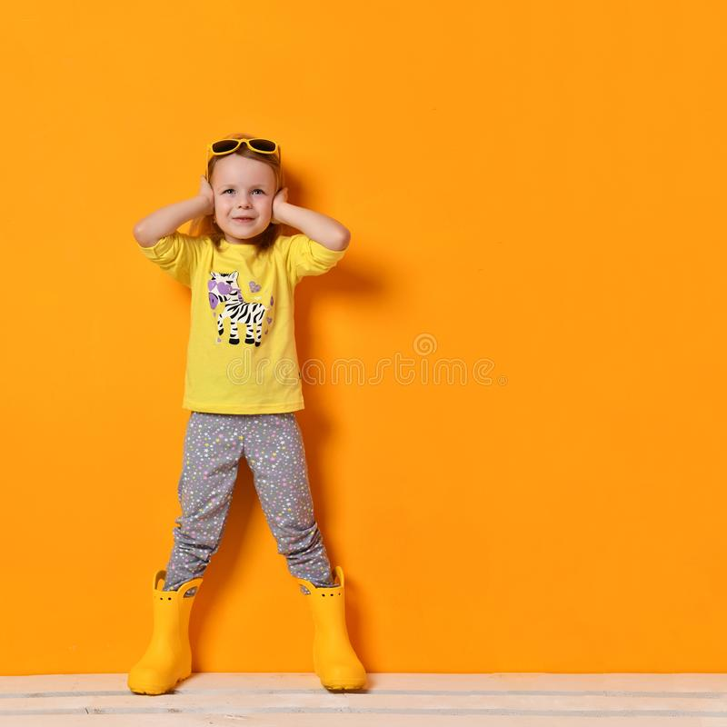 Young child baby girl kid in yellow rubber boots sunglasses and t-shirt posing on yellow stock image