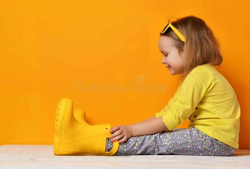 Young child baby girl kid in yellow rubber boots sunglasses and t-shirt sitting on yellow royalty free stock images