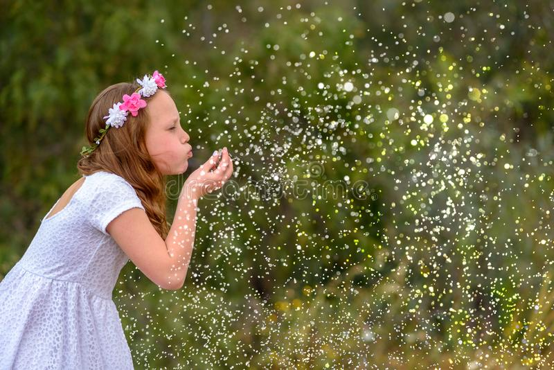 A young child is blowing sparkles or snowflakes in a nature background, holiday concept. stock photo