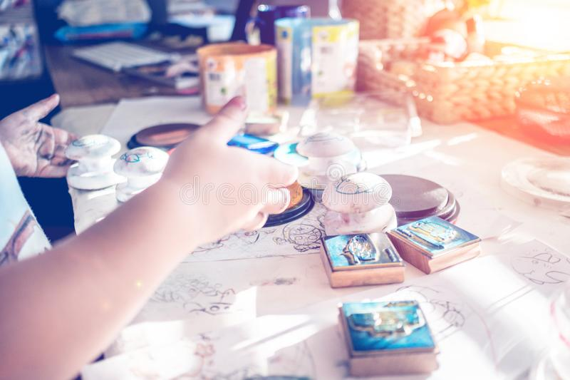 Boy is having fun while playing with stamps and tempera paints on wooden work desk producting multicolor creations royalty free stock image