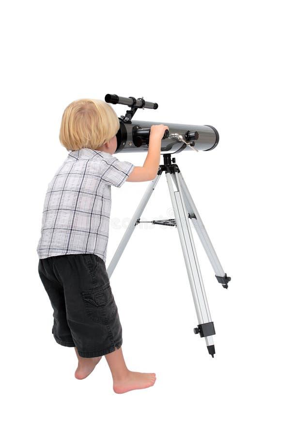 Young child or boy looking through a telescope stock photos