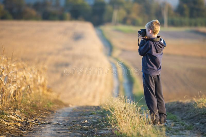 Young child boy with photo camera taking picture of wheat field on blurred rural background royalty free stock photos