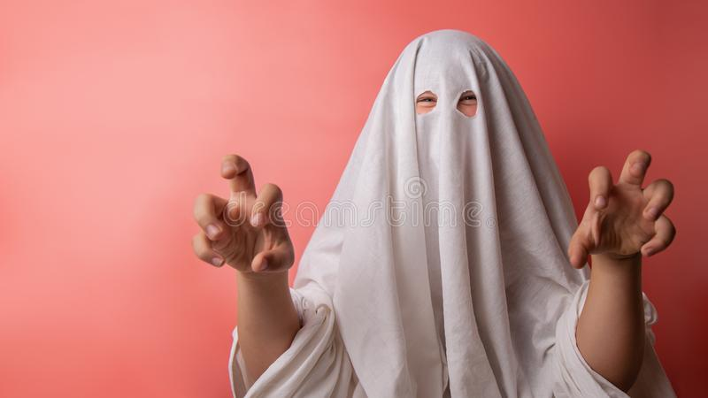 Young child dressed in a ghost costume for halloween on pink background stock photos