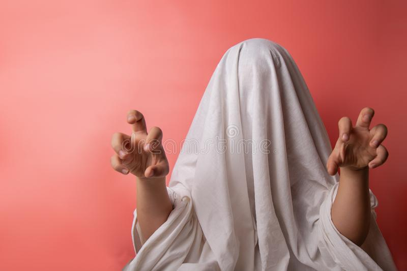 Young child dressed in a ghost costume for halloween on pink background royalty free stock image