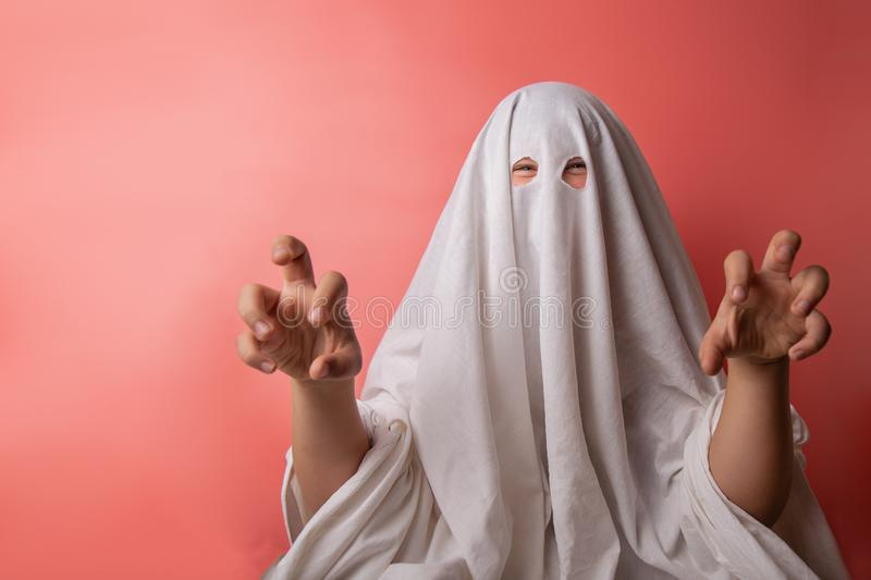 Young child dressed in a ghost costume for halloween on pink background stock photo